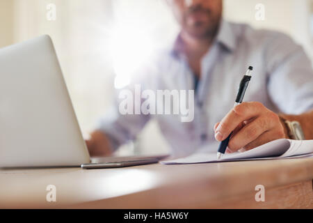 Close up shot of young business man hands with pen writing notes on a paper. Male executive sitting at table at - Stock Photo