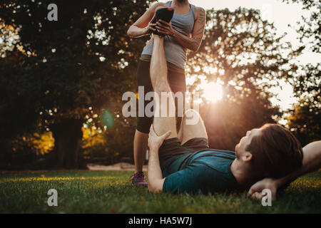 Young man having a strain and being stretched by female trainer. Woman stretches man's leg, muscle spasm after sport - Stock Photo