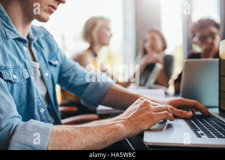 Close up shot of young man using laptop with classmates studying in background. Students learning in college library. - Stock Photo