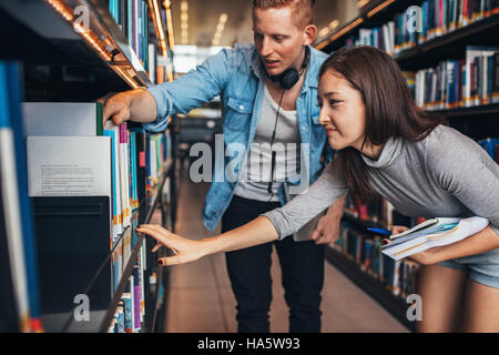 Young students finding reference books in university library. Man and woman finding information for their studies. - Stock Photo
