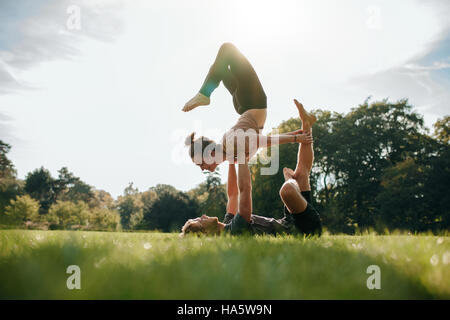 Caucasian couple doing acro yoga in park. Man and woman doing various yoga poses in pair outdoors. - Stock Photo
