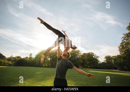 Man and woman doing pair yoga outdoor in a park. Fit young couple practising acroyoga. Man lifting and balancing - Stock Photo