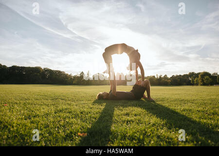 Outdoor shot of young man and woman doing yoga in pair. Couple doing acrobatic yoga exercise at park. - Stock Photo