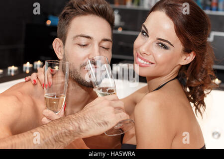 Couple drinking champagne in jacuzzi, romantic moments - Stock Photo