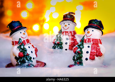 Three smiling snowmen in snow, Happy New Year 2017, Christmas, bright defocused lights in background - Stock Photo