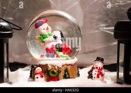 Snowman in snowdome, Christmas decoration at home, Happy New Year 2017, closeup, fake snow - Stock Photo