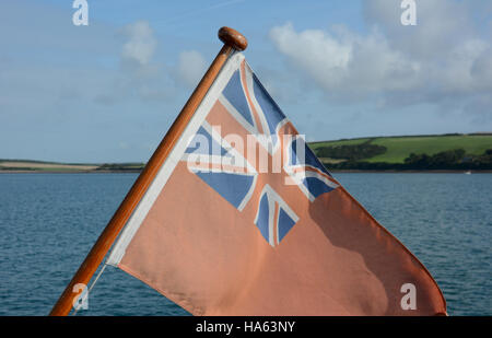 Red Ensign on yachts flag pole with blue sky & white clouds, green hills and ripple azure sea - Stock Photo