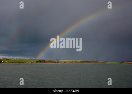 Bright double rainbow over the Upper Cleddau in Pembrokeshire against a dark sky over calm water - Stock Photo