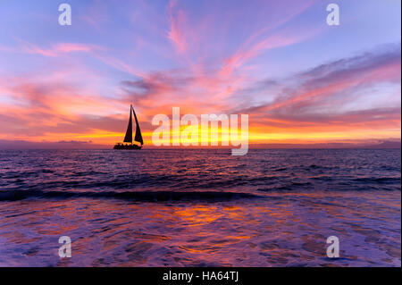 Ocean sunset sailboat silhouette is sailboat sailing along the ocean water with a colorful vivid sunset sky. - Stock Photo