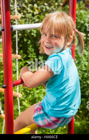 Portrait of cute blond girl with blue eyes wearing blue tshirt sitting on monkey bars on a summer day. Girl looking - Stock Photo