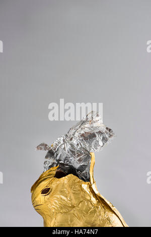 Chocolate Easter bunny, wrapped in shiny golden and silver aluminum foil, partially nibbled away, foil ripped open - Stock Photo