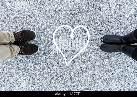 Male and Female boots standing at heart symbol on asphalt covered gritty snow surface. Rough snowy. Cold Winter. - Stock Photo