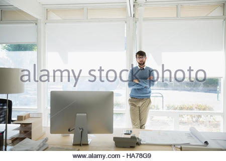 Portrait confident male architect with arms crossed at office window - Stock Photo