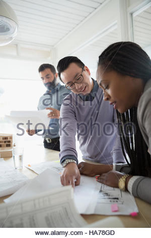 Architects discussing blueprints and paperwork in meeting - Stock Photo
