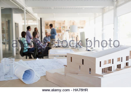 Architects meeting in open plan office behind blueprints and architectural model - Stock Photo