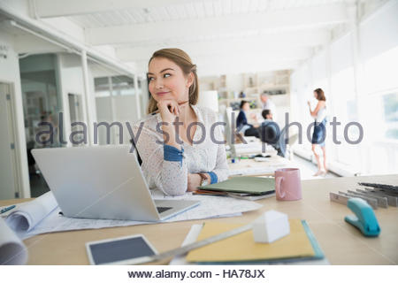 Smiling female architect working at laptop in office - Stock Photo