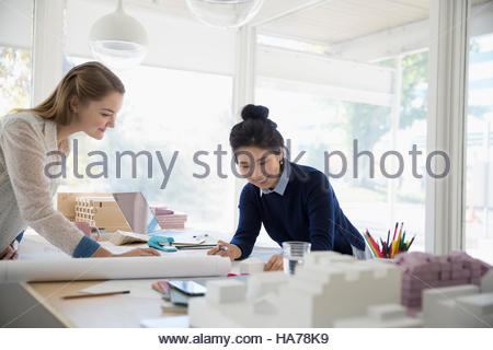 Female architects reviewing blueprints in conference room - Stock Photo
