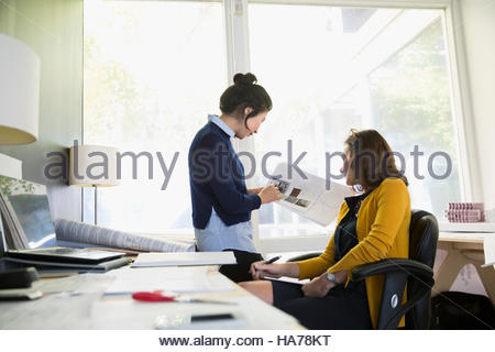 Female architects meeting and discussing blueprints in office - Stock Photo