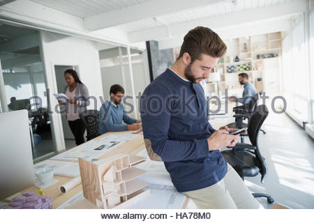 Male Architect texting with cell phone near architectural model in office - Stock Photo