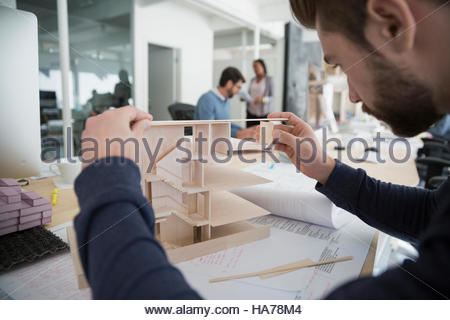 Male architect assembling architectural model in office - Stock Photo