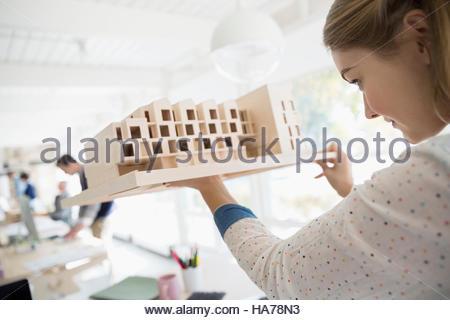 Female architect examining architectural model - Stock Photo