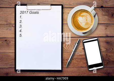 Business concept - Top view clipboard writing 2017 Goals, pen, coffee cup, and phone on wood table. - Stock Photo