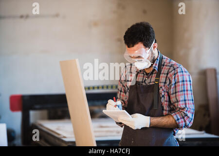 Horizontal view of professionally dressed carpenter varnishing a board - Stock Photo
