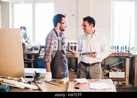 Happy male carpenter showing something to coworker at his notebook papers in workshop - Stock Photo
