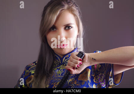 Samurai woman dressed in traditional colorful flower pattern asian silk dress, holding hand on sword facing camera, - Stock Photo