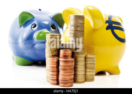 Stack of coins in front of piggy banks - Stock Photo