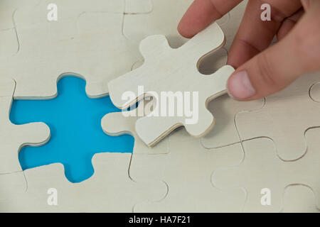 Woman placing missing piece in jigsaw puzzle - Stock Photo