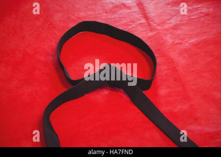 Karate black belt on red background - Stock Photo
