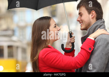 Side view of a couple encounter in the street under an umbrella in a rainy day - Stock Photo
