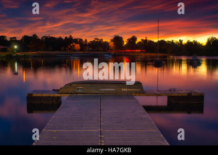 The boat pier at Sloan's Lake in Denver, Colorado awaits visitors as the sunrise paints the sky with incredible - Stock Photo