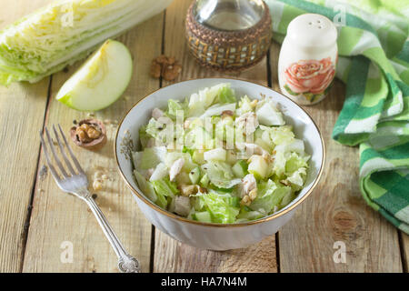 Salad with cabbage, chicken, apple, cucumber and walnuts. Healthy food concept. Top view. - Stock Photo
