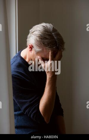 Man with headache or hiding face or very upset or migraine attack - Stock Photo