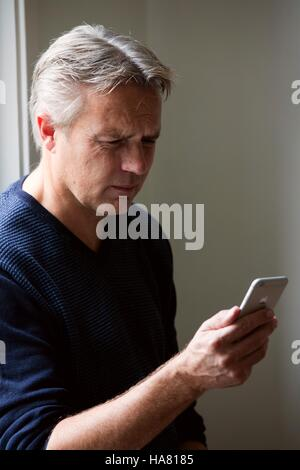 Adult man looking worried at his cell phone - Stock Photo