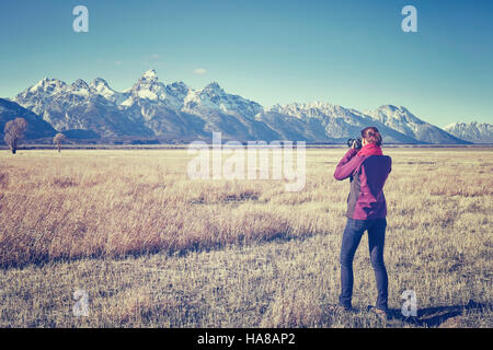 Vintage toned female fit hiker taking pictures with DSLR camera in the Grand Teton National Park, Wyoming, USA. - Stock Photo