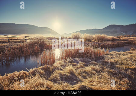 Retro toned foggy and frosty morning over lake in Grand Teton National Park, Wyoming, USA. - Stock Photo