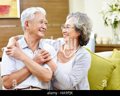 loving asian couple looking at each other smiling with appreciation - Stock Photo
