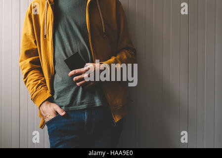 Casual young adult man posing with mobile phone in hand, wearing jeans and yellow shirt with zipper, retro toned, - Stock Photo