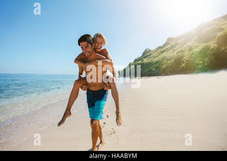 Portrait of man carrying girlfriend on his back along the sea shore. Man giving piggyback ride to girlfriend on - Stock Photo
