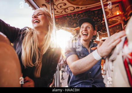 Young man and two women on carousel at fairground. Young couple riding horse carousel in amusement park and laughing. Stock Photo