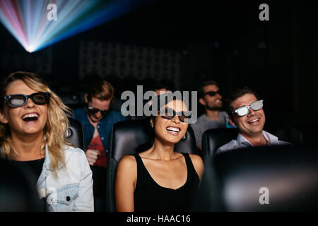Group of young friends watching 3d movie in theater and laughing. Young men and women wearing 3d glasses in cinema - Stock Photo