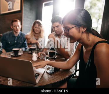 Group of friends in cafe watching something online on laptop. Young men and women at restaurant looking at laptop. - Stock Photo