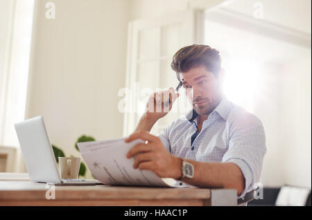 Shot of a young man sitting at table looking at documents and thinking. Business man going through paperwork at - Stock Photo