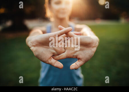 Young woman stretching arms outdoors. Fitness female doing warmup exercise at the park, focus on hands. - Stock Photo