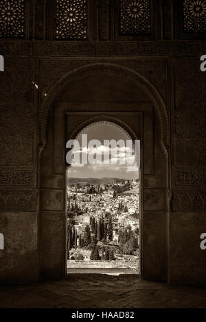 view of Granada through arched window of the alhambra palace - Stock Photo