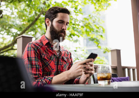 Man using mobile phone in bar - Stock Photo