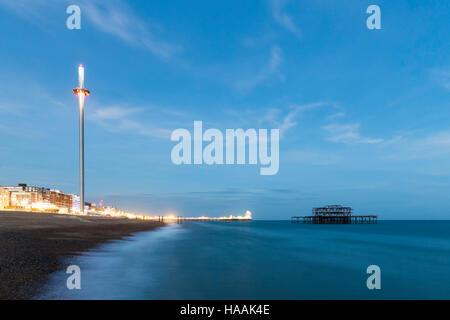 Night Photo of Brighton Skyline with old West Pier, Central Pier with fun fair lights and the new i360 attraction - Stock Photo
